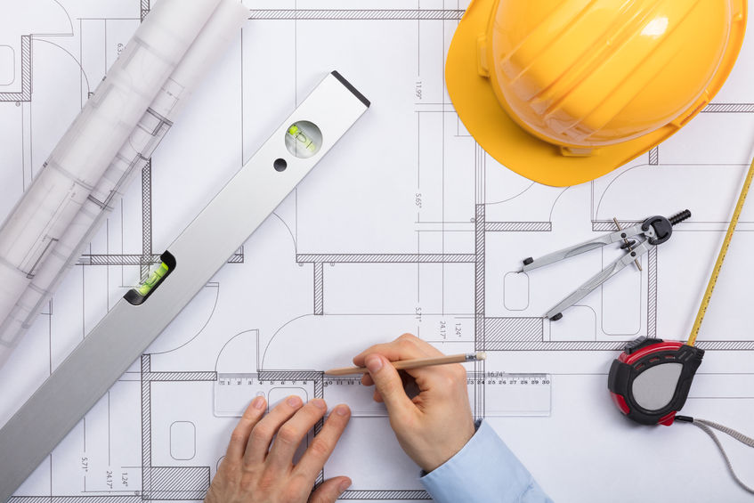 Person working on architectural drawing - MV Mechanical