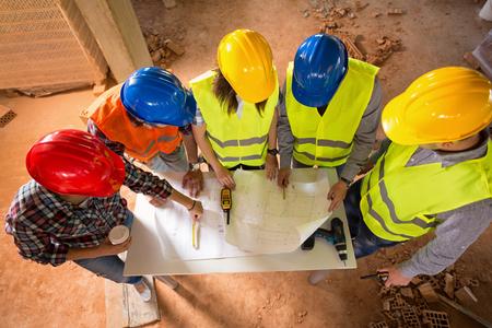 Construction crew reviewing architectural plans - MV Mechanical Inc.