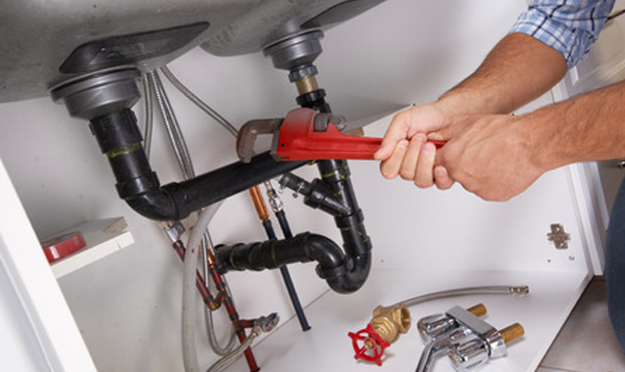 Plumber working on piping under a sink - MV Mechanical Inc.